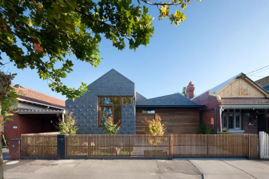 At the front of this modern house, a combination of grey brick and wood paneling covers the front exterior. Protruding bricks at the front add texture and depth, while the wood paneling that matches the trims of the windows and the fence adds warmth and a natural look to the home.