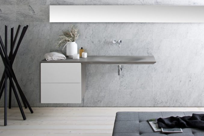 This modern, seamless grey stone sink is wall mounted with two white drawers and a chrome faucet.