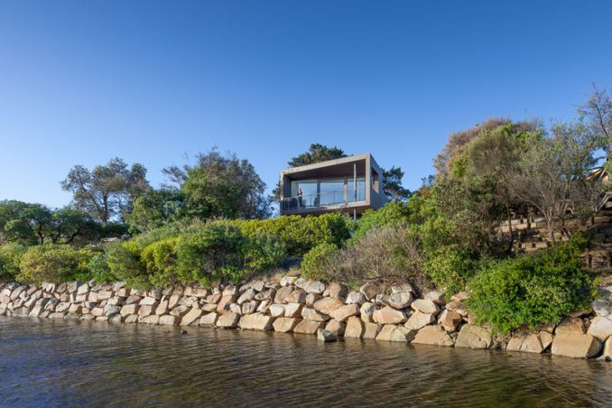 Open Studio Pty Ltd Architecture have created a modern house near Melbourne, Australia, that's surrounded by water and bushland, and was designed for a couple, their dog and visiting friends and family.
