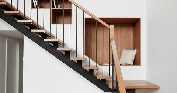 This modern wood and steel staircase features a wood-lined seating nook and bookshelves that have been built into the wall.