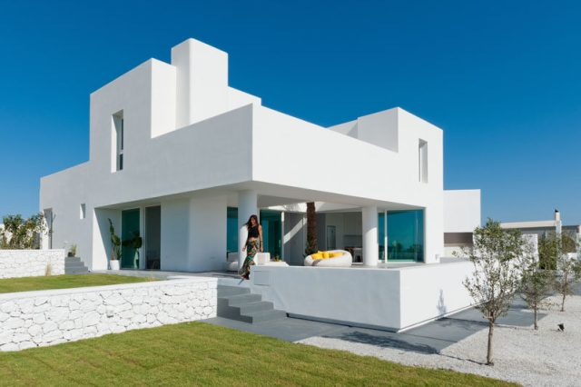 Kapsimalis Architects have design a new modern summer house in Santorini, Greece, that sits on a slightly sloped site and has views of the sea. #WhiteHouseExterior #ModernHouse #ModernArchitecture