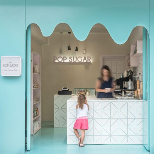 The curvy, blue metallic facade of this sweets store resembles melting chocolate, while the color carries through to the floor and the geometric pattern on the bar, inviting people inside. #RetailDesign #StoreDesign #InteriorDesign
