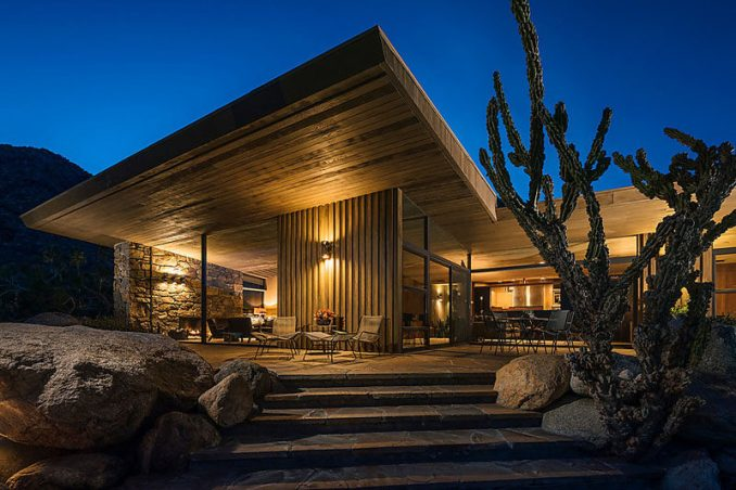 Positioned within the desert landscape, this house is an example of mid-century modern architecture. Wood features have been combined with stone walls and plenty of glass. #Wood #Stone #MidCenturyModern #House