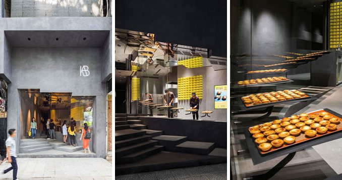 This modern bakery has a large concrete storefront with double height ceilings and a simple yellow and grey color palette, making the store stand out when compared to surrounding shops. #ModernBakery #StoreDesign #RetailDesign