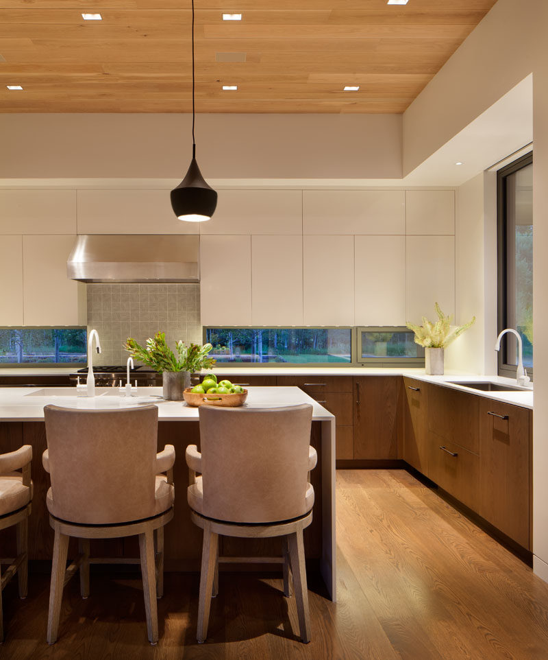 In this kitchen, minimalist white cabinets, a white island and white countertops have been combined with lower wood cabinets to create a contemporary look. #Kitchen #ContemporaryKitchen