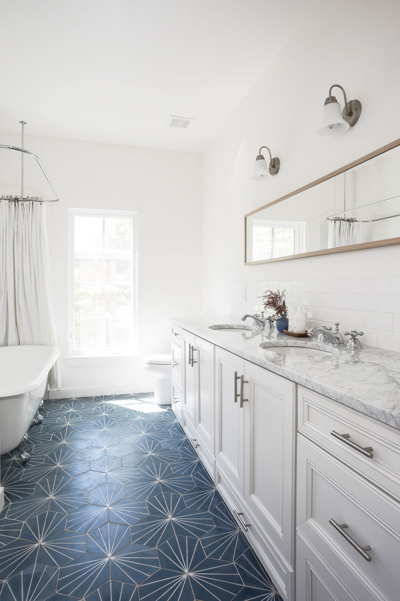 A blue dandelion tile adds a pop of color to this contemporary white bathroom. #BlueTile #BathroomDesign