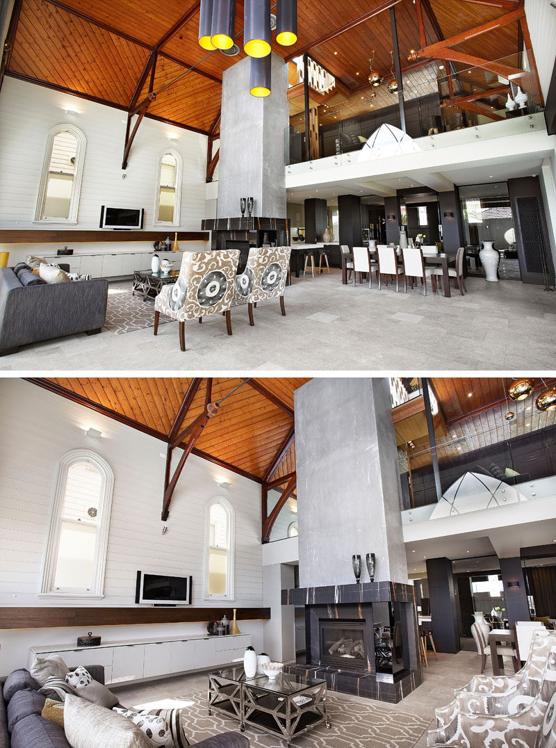 This converted church has a centrally located fireplace and from this angle, you can see that there's a mezzanine above the kitchen and dining area. #ChurchConversion #InteriorDesign #Fireplace