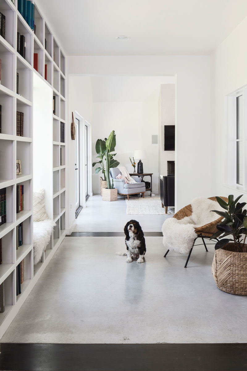 Stepping inside this contemporary house, the entryway has a window seat surrounded by bookshelves, and it opens up into the main social areas of the house. #Bookshelf #Entryway #InteriorDesign
