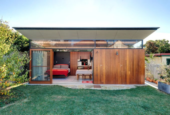 This modern backyard studio in Australia has a home office, living quarters, bathroom with laundry, an outdoor shower and a shed with an indoor/outdoor workspace. #BackyardStudio #GuestHouse #Architecture