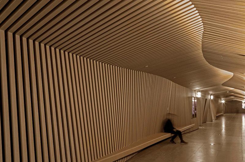 The designers of this modern cinema used wood slats to represent their inspirations, movie scripts and animation flip books. #WoodSlats #Cinema #InteriorDesign #MovieTheatre