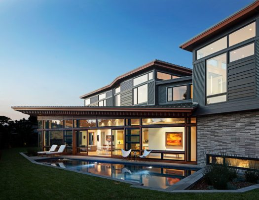 This modern house is comprised ofa dramatic series of folded roof planes, and a collage of textured metal and wood exterior surfaces. #ModernHouse #HouseDesign #ModernArchitecture