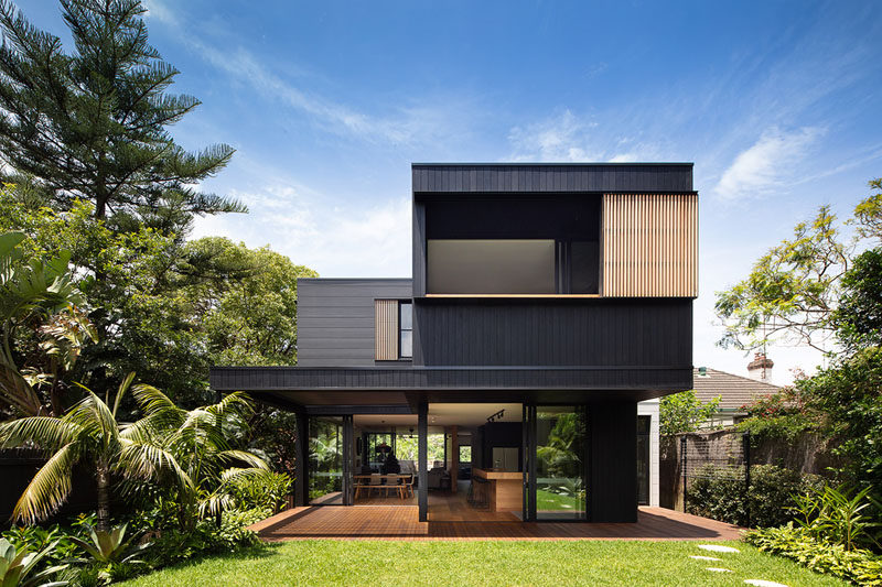 The exterior of this modern house is clad inBlackened Cambia Ash and Scyon Stria, while sliding glass doors open the home up to the backyard. #ModernHouse #ModernArchitecture