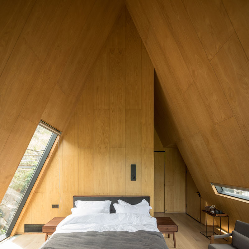 This interior of this modern cabin has wood panels covering the angled walls, while windows provide glimpses of the surrounded landscape. #ModernCabin #CabinInterior #Bedroom