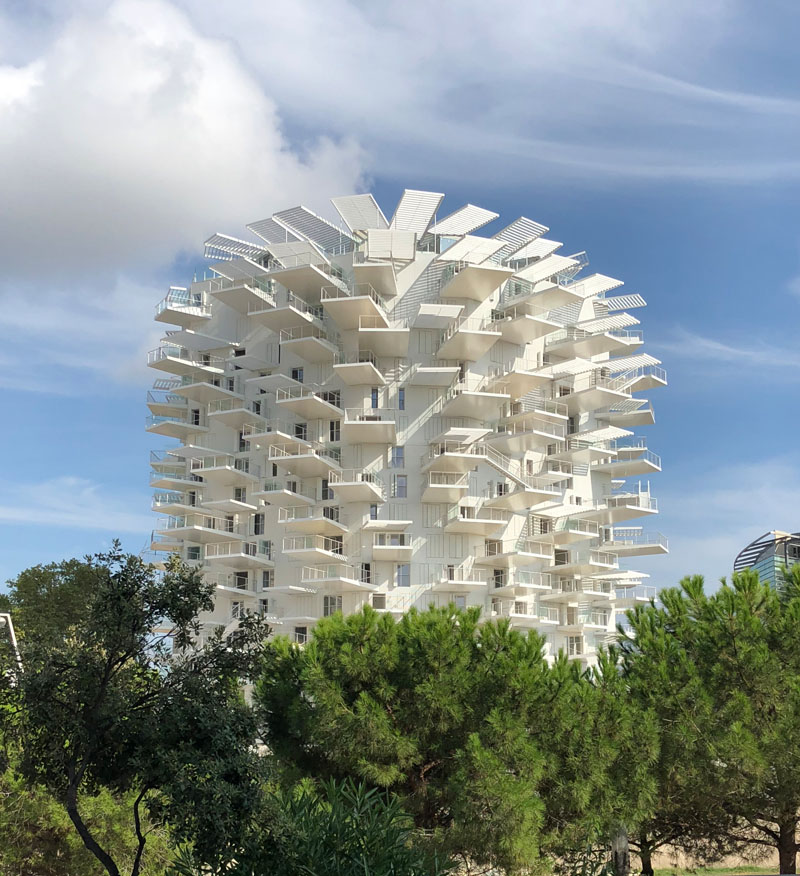 This modern apartment building in France has cantilevered balconies that surround it, while stairs connect the various outdoor spaces. #ModernArchitecture #BuildingDesign #Balconies