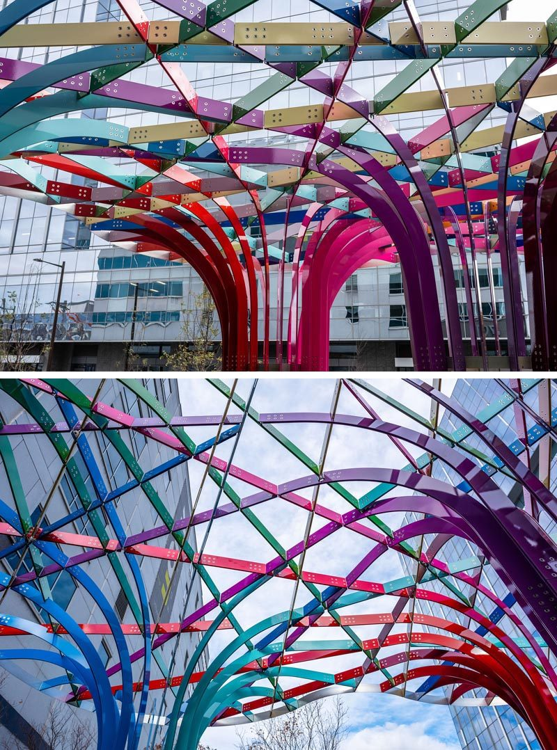 This modern public art installation invites visitors to walk through a grove of archways that have been woven together from intersecting bands of powder-coated aluminum in 28 colors. #PublicArt #PublicInstallation #PublicSculpture #ModernArt #ModernSculpture #Design