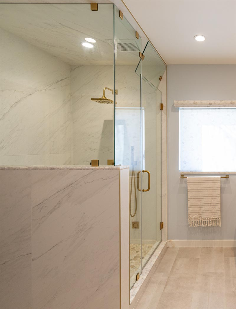 Brass accents have been used throughout this modern bathroom, like in the shower head and the clips that hold the glass in place. #Bathroom #ShowerDesign #EnclosedShower