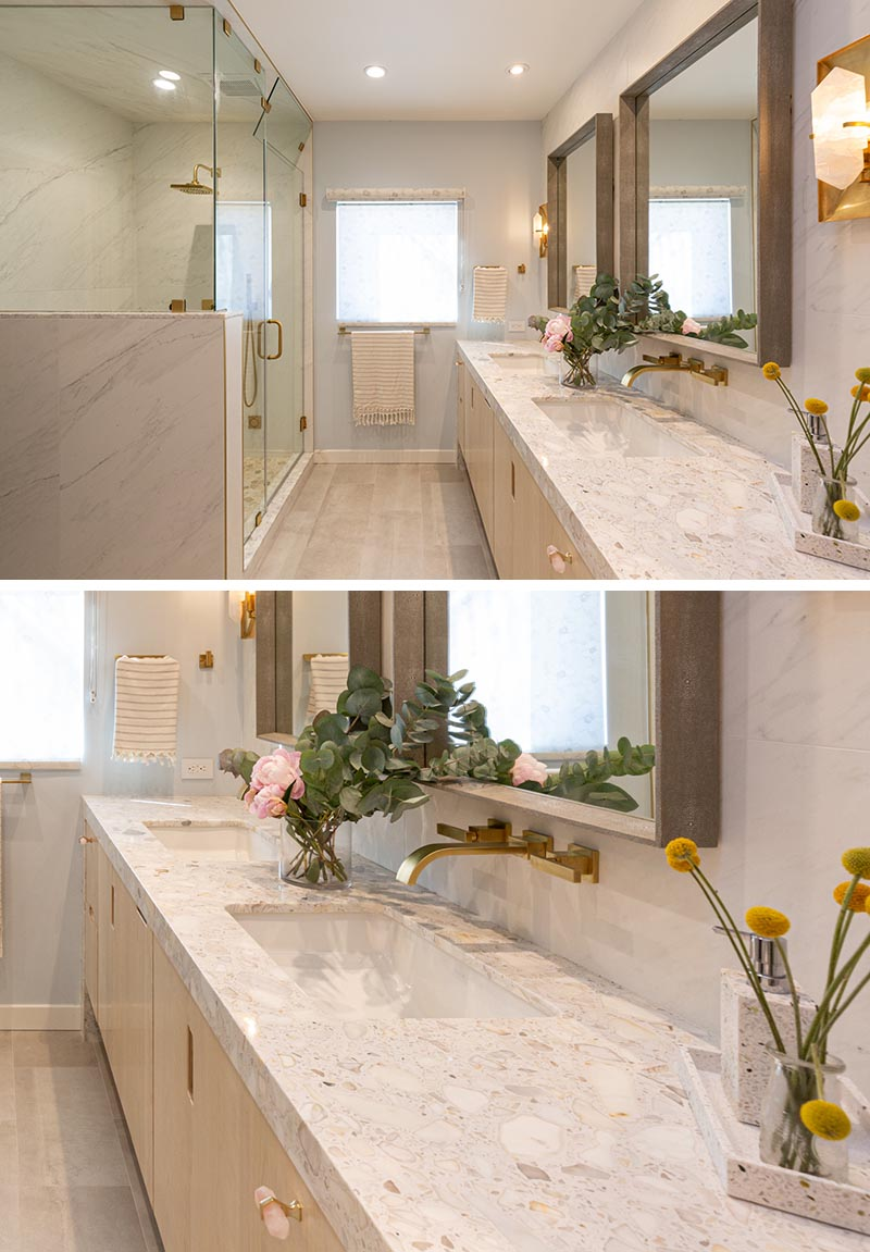 This double-vanity, which travels to the end of the bathroom, has a stone countertop, with undermount sinks, and two square wood-framed mirrors. #ModernBathroom #BathroomVanity