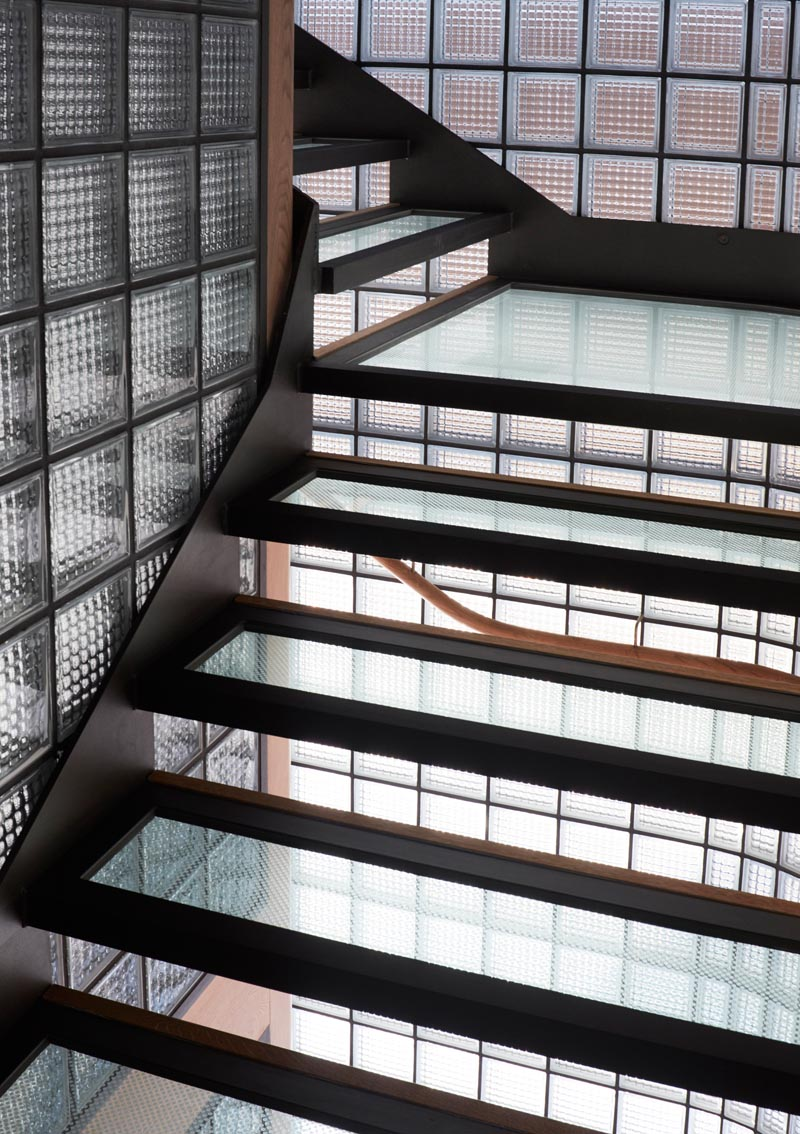 This modern house features a stairwell surrounded by glass blocks with black grout, and steel, wood, and glass treads. #ModernGlassBlock #GlassBlock #Stairs #Stairwell