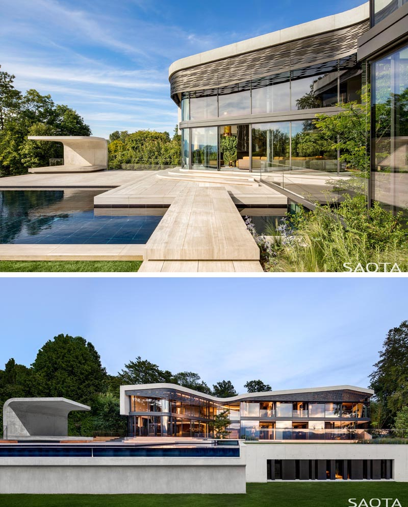 Walls of glass open this modern house to an expansive outdoor space with a curved concrete cabana sitting next to the swimming pool. From this angle, you are able to see the laser-cut aluminium shading screen that follows the curves of the roof. #Architecture #PoolCabana #SwimmingPool #ShadeScreen #ModernHouse