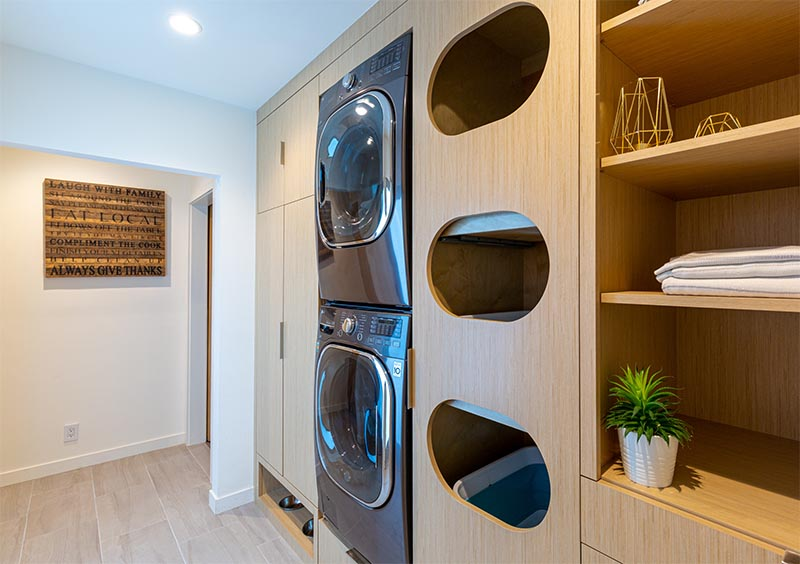 Laundry Ideas - This modern laundry room is designed with separate cubbies for sorting clothes, built-in washer and dryer, the pull-out step located below them, plenty of storage space, open shelving, and a pet feeding area. #LaundrySorter #LaundryDesign #ClothesSorter #BuiltInWasherDryer #ModernLaundry