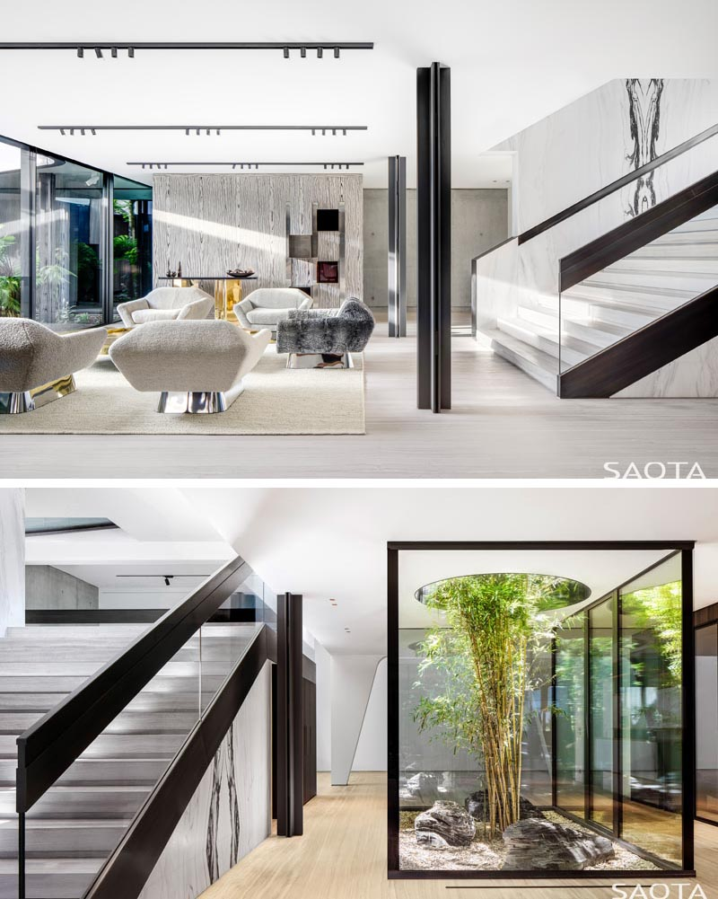 This modern house has a secondary living room and a small interior garden surrounded by glass, has a tree that's grown up through a circular opening. #InteriorGarden #LivingRoom #Stairs