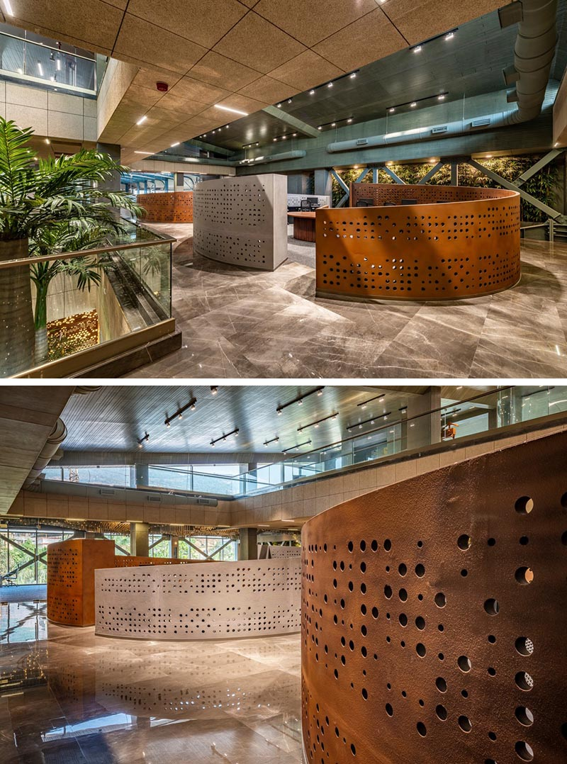 The curved perforated panels of this modern workplace feature a grid of differently sized circles that let the light travel through. #WorkplaceDesign #OfficeDesign