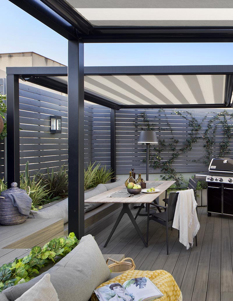 This modern outdoor terrace has a dining area with bench seating that matches the nearby lounge, while the grey wood slat fence adds to the modern feeling of the space. #OutdoorTerrace #OutdoorDining #OutdoorEntertaining