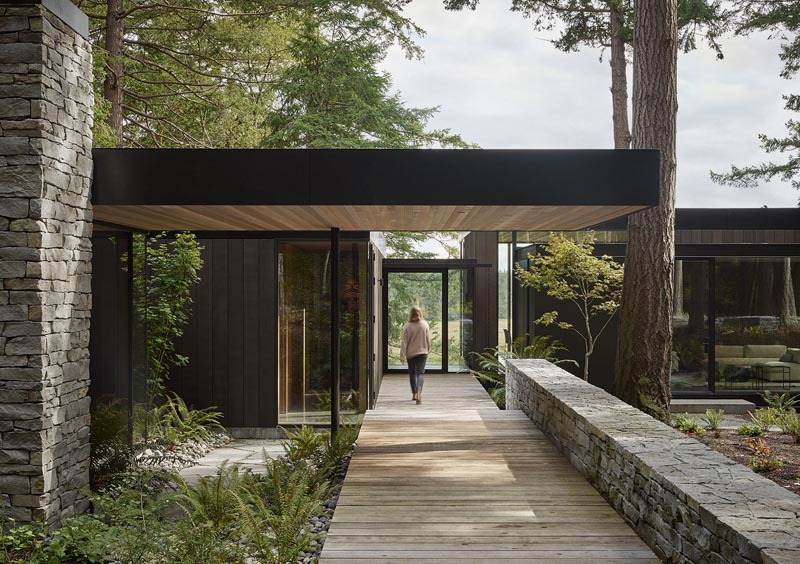 This modern house is situated on the edge of a forested hillside, overlooking chicken sheds, a weathered red barn, cattle fields, and a fishing pond. #ModernHouse #DarkWoodSiding #Architecture