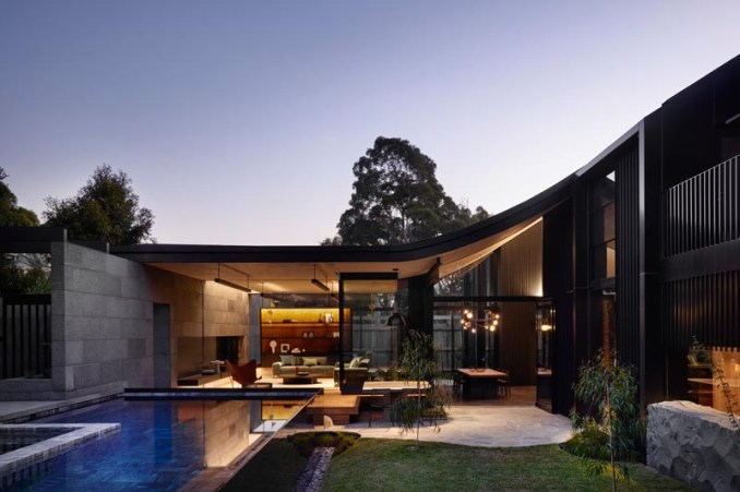 This modern house has a living room that connects to an outdoor space with a yard and swimming pool. #Architecture #OutdoorSpace #Landscaping #SwimmingPool