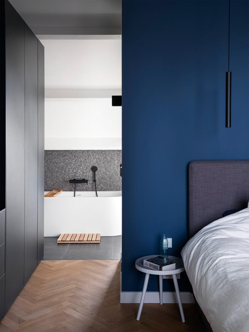 In this modern master bedroom, a royal blue accent wall has been combined with black cabinetry, white trim, and herringbone wood floors. #MasterBedroom #BlueWalls #BedroomDesign