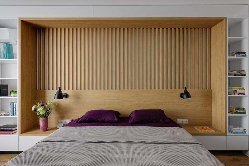 The design of this custom wall in a modern bedroom, combines wood and white details, and integrates the bed frame, a headboard, side tables, and bookshelves. #BedroomDesign #ModernBedroom #Headboard #Bookshelves
