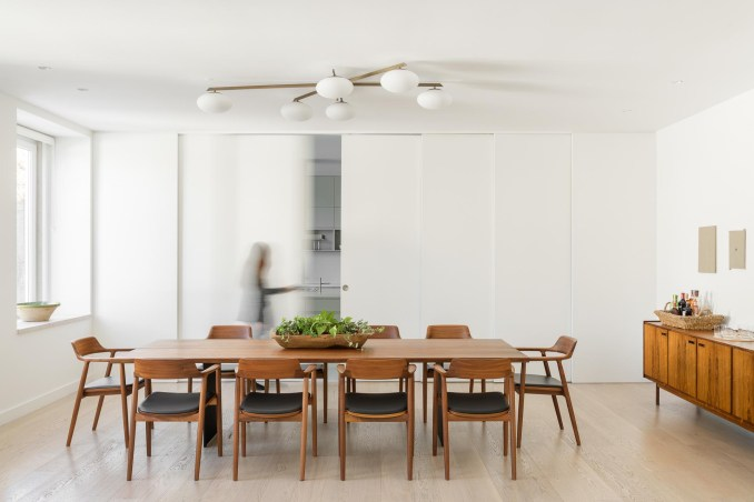A kitchen is hidden from the dining room by sliding white panel doors.