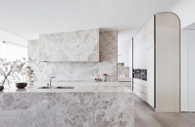 Limestone has been used in this modern kitchen to cover the island, and act as the backsplash that travels up to the angled ceiling.