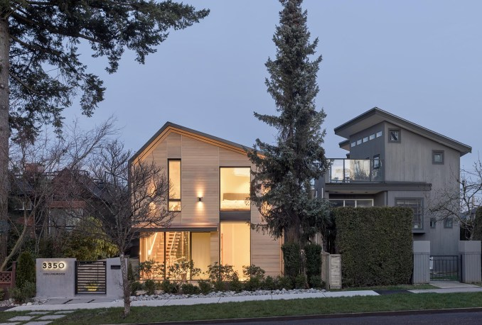 A modern house with a wood facade that's lit up with exterior lighting.