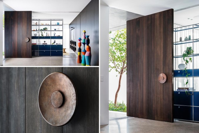 An oversized floor-to-ceiling dark pivoting timber front door welcomes guests to this modern home.
