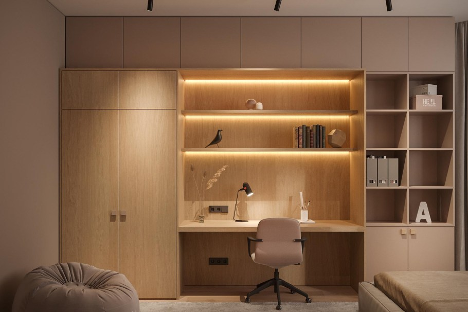 A modern built-in home office surrounded by bookshelves and closets, also has the shelving with hidden lighting.