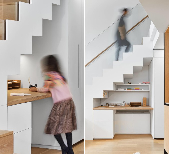 A modern loft apartment with a built-in desk under the stairs.