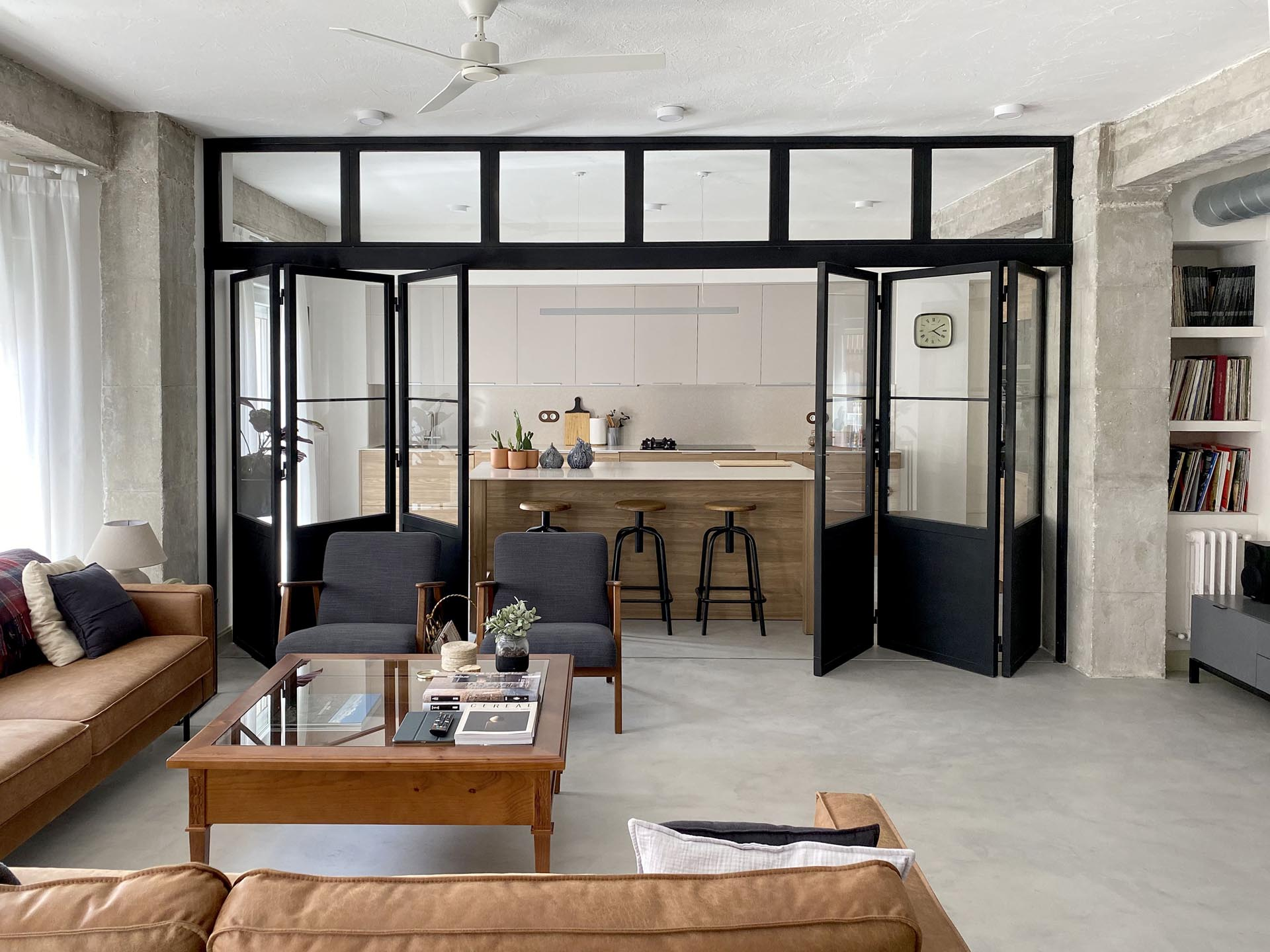 A modern kitchen can be closed off from the living room by black-framed doors with windows.