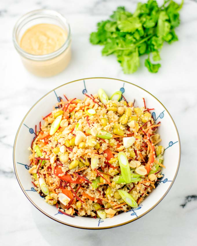 Far shot of the Thai Quinoa Salad with Basil and a jar of Thai Peanut sauce in the background.