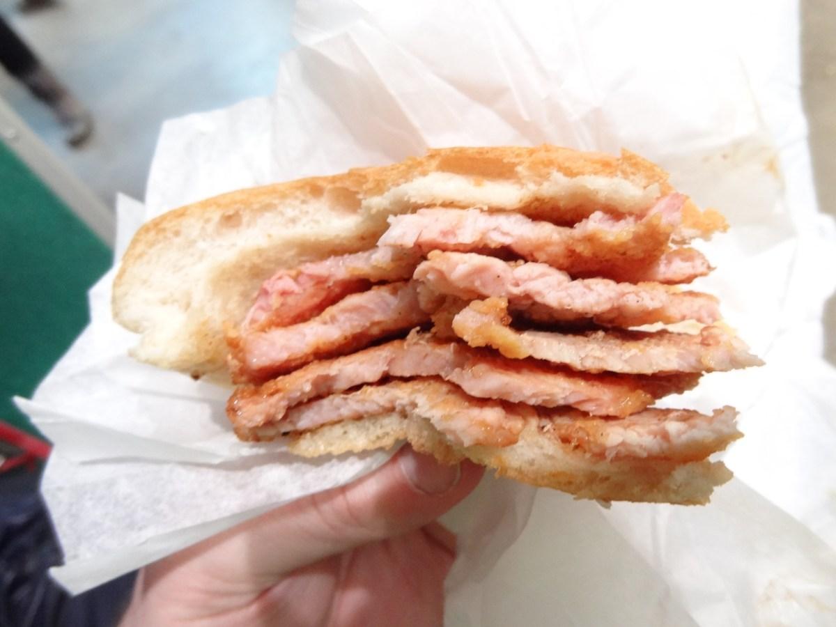 Delicious Destinations Toronto - Thin slices of cornmeal bacon in a bun