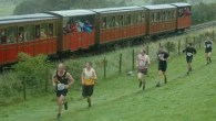 Competitors race against a steam train in Wales