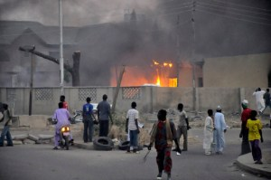 People watch as smoke rises from the police headquarters after it was hit by a blast in Nigeria's northern city of Kano