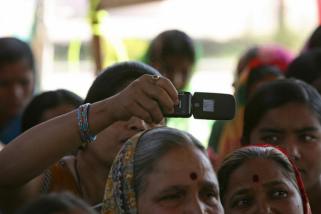 Woman takes photo with cellphone at a community meeting credits World Bank photo collection via Flickr ((CC BY-NC-ND 2.0) )