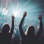 Two women worshipping at a concert