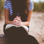 Woman sitting outside, praying.