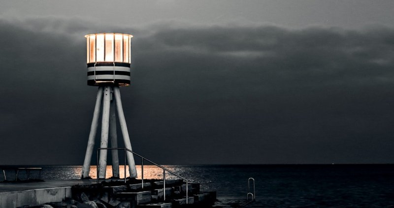 a lighthouse by the ocean, on grey, bleak day