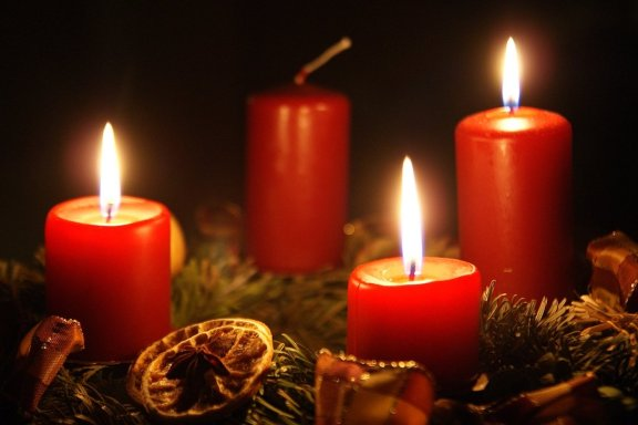 lit red candles on a christmas wreath in the dark
