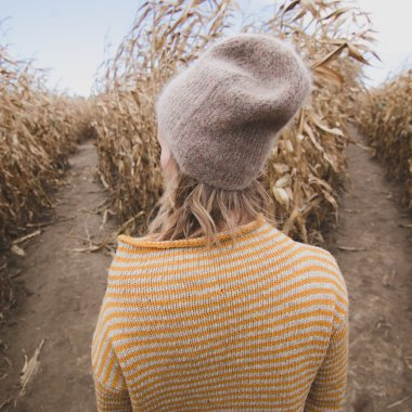 Girl facing a corn field, two paths.
