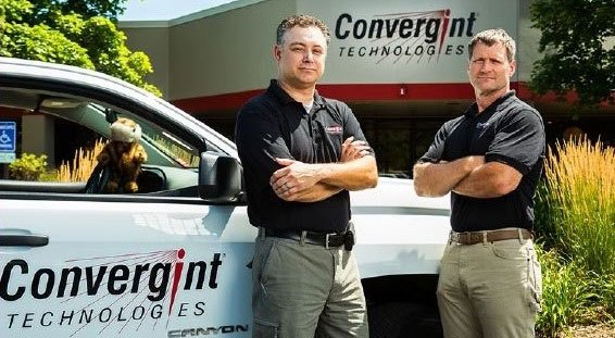 2 colleagues stand outside of Convergint Technology Vehicle with Gopher in front seat