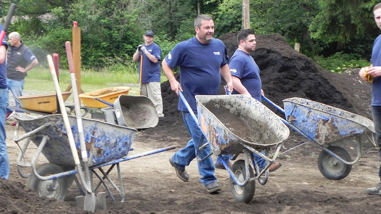 Convergint colleague pushing a wheelbarrow